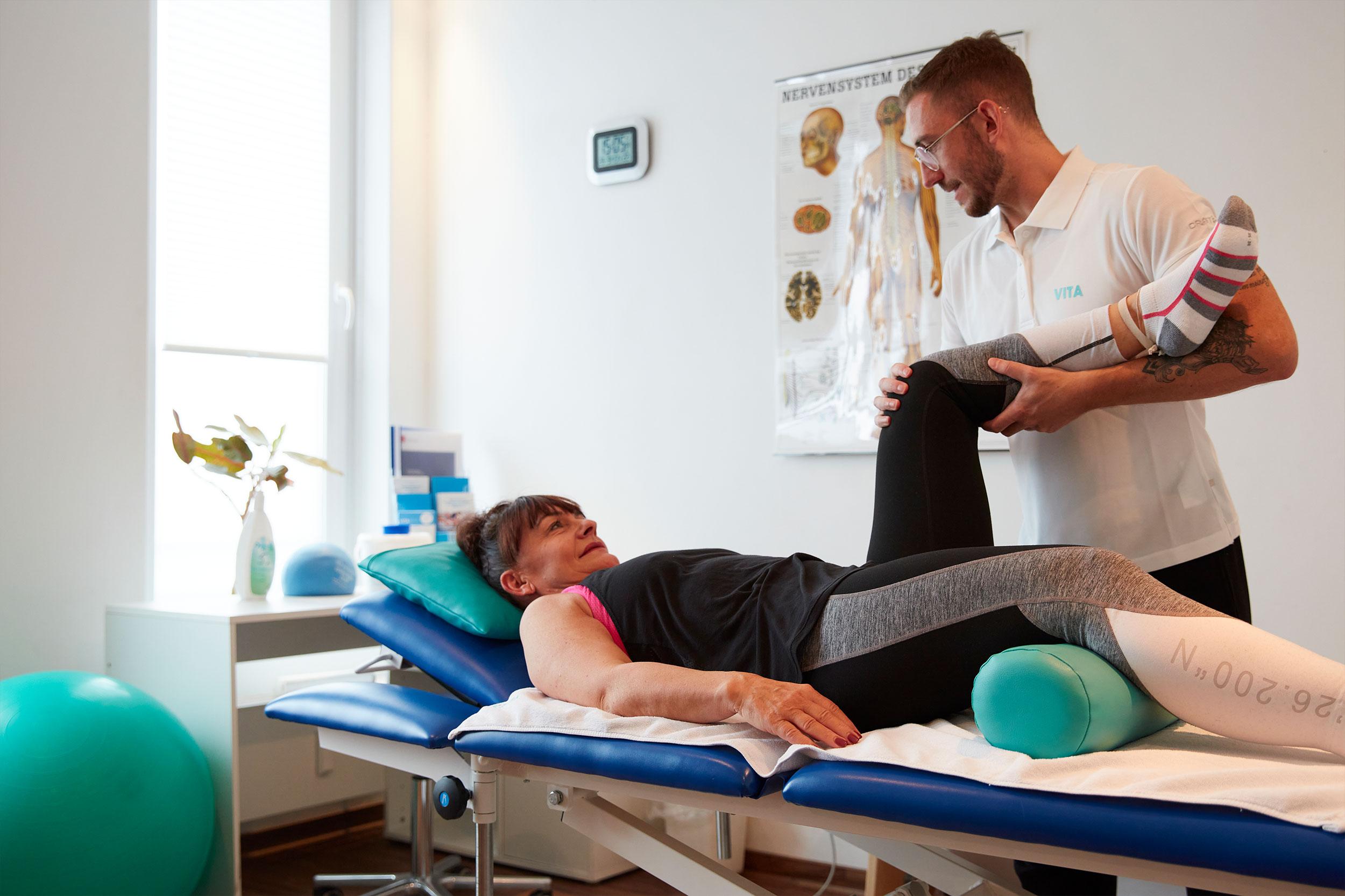 Bild zeigt eine physiotherapeutische Behandlung. Zu sehen ist ein Behandlungsraum, eine Physiotherapeut und eine Patientin.